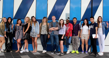 a group of interns posing on a wall