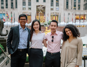 Interns dressed in business casual smile for a group photo in New York