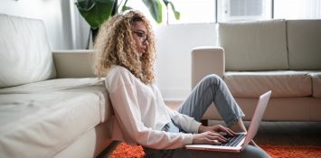 girl sat on floor with laptop