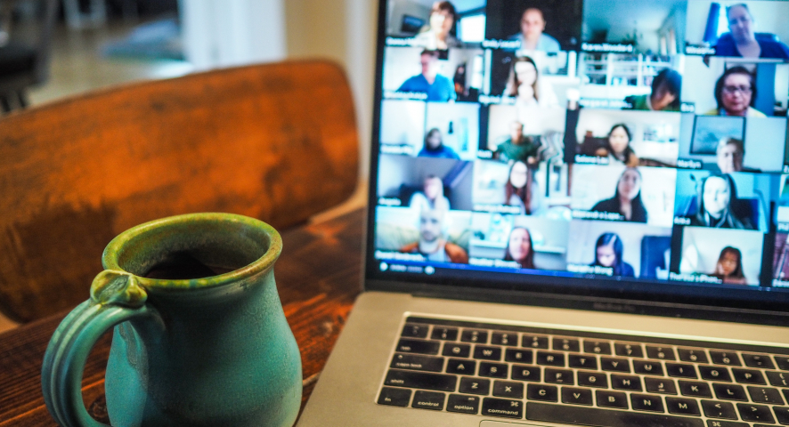 Image of a laptop while on a zoom call, next to a blue mug.