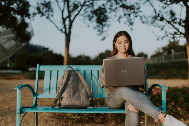 a girl sitting on a blue bench with a backpack next to her, working on a laptop