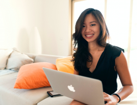A woman sitting on a grey couch smiles and types on a laptop