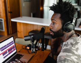 A man wearing headphones speaks into a microphone while recording on a computer program