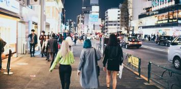 Three women walk down a bright city street