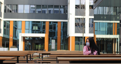 A woman in a pink sweater and a mask sits on a bench
