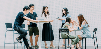 Students in business casual clothing gather around a table