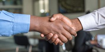 Two men in professional attire shake hands.