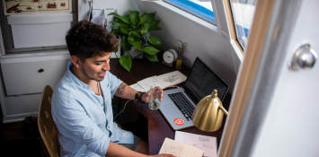 A young man in a bottom down shirt works at a desk