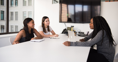 Three women chat at a table in an office