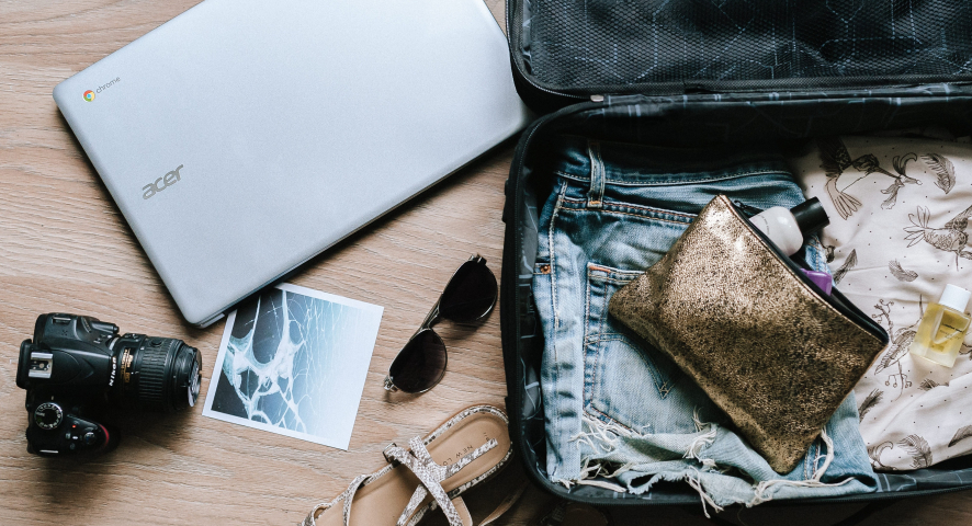 An open suitcase shows travel accessories and a laptop