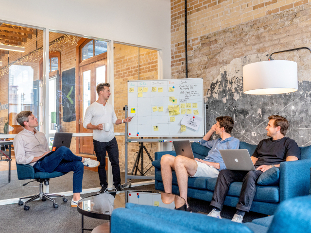 A group of young professionals sits on couches looking at a white board