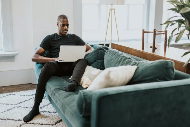 A man in a black shirt sits on a green sofa, typing on a laptop