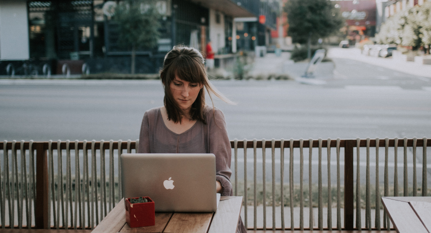 A woman sits at an outdoor table typing on a laptop