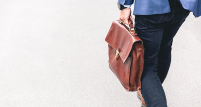 A person wearing a blue suit carries a brown leather briefcase.