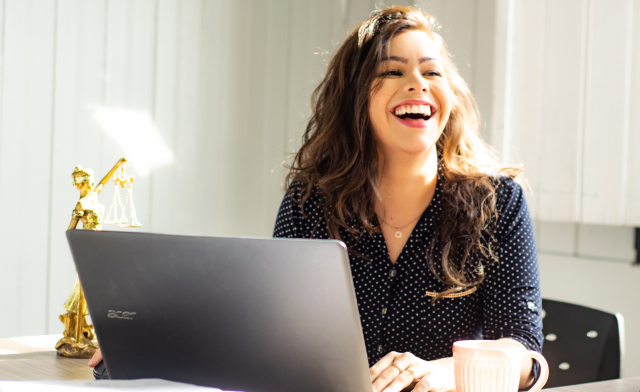 A young woman working at a laptop laughs at the camera
