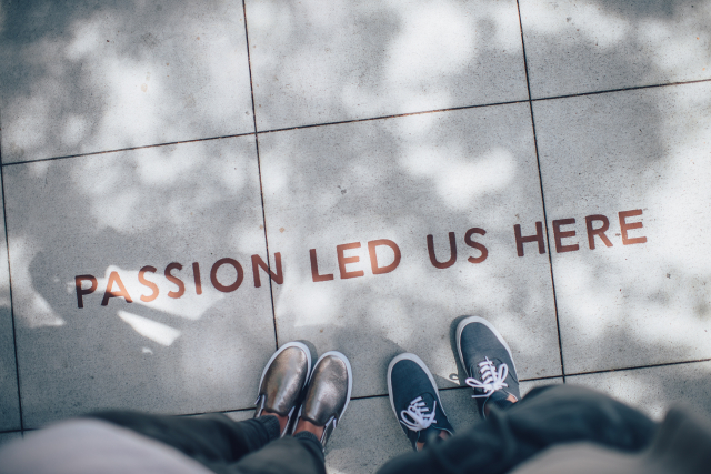 "Two pairs of shoes standing on a sidewalk next to painted words that say ""passion led us here."""