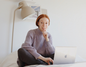 A woman in a purple sweater sits on a bed working on a laptop