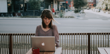 A woman works on a laptop at a coffee shop table