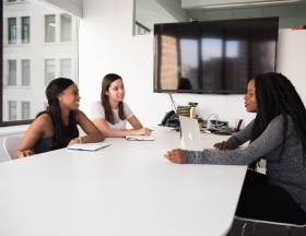 Three women sit at an office table