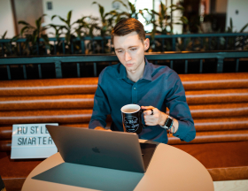A man working on a laptop drinks coffee