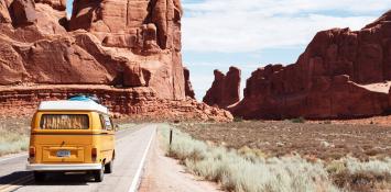 A yellow van drives down a desert highway.