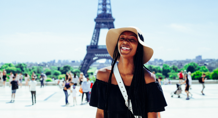 A smiling woman stands in front of the Eiffel Tower