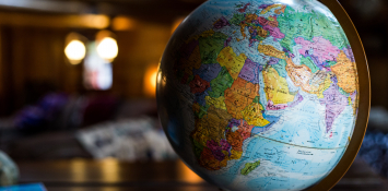 A large globe of the earth sits on a desk.