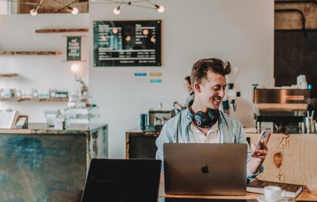 A man with headphones works on a laptop in a coffee shop