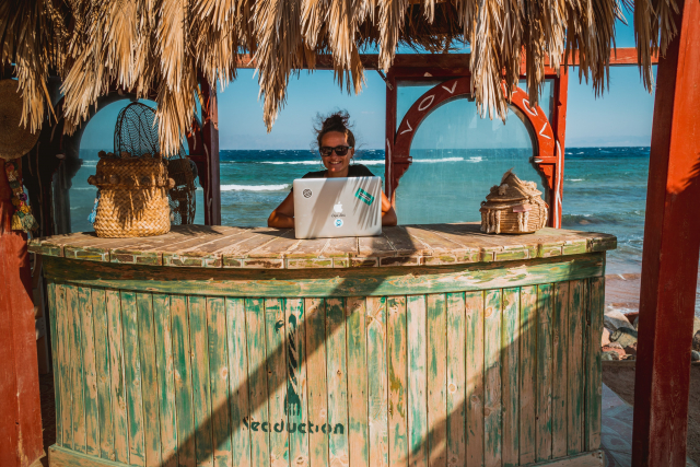 A woman works on a laptop in a beach hut.