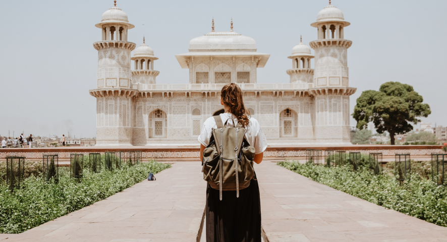 A woman with a backpack stands in front of a temple