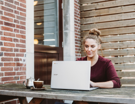 A woman sits outside working on a laptop