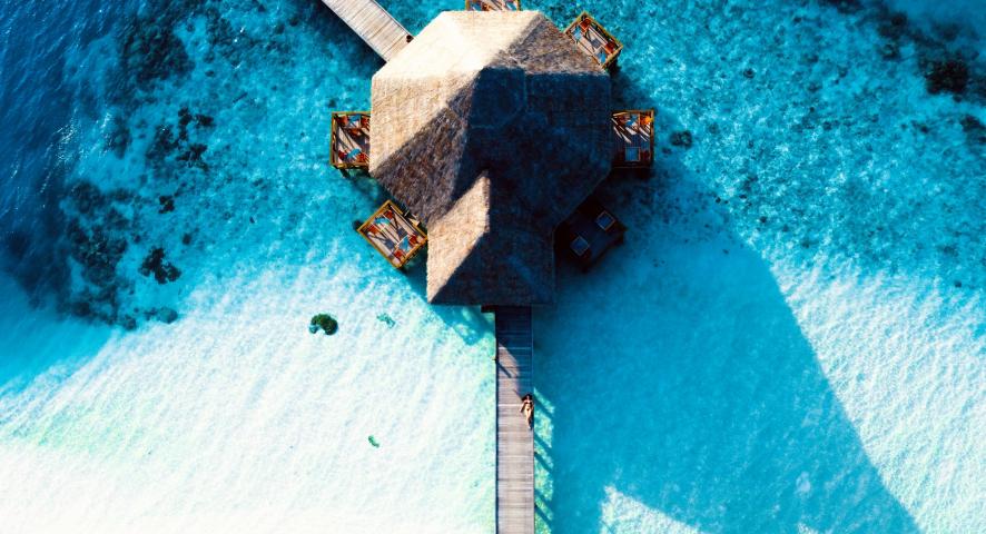 An aerial photo of a round cabin in a blue ocean.
