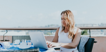 A woman sits at a coffe table on a balcony, working on a computer.