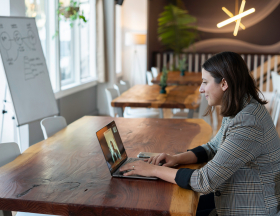 A woman in a blazer takes a video call on a laptop.