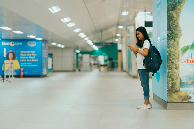 A woman with a backpack stands alone on a train station platform