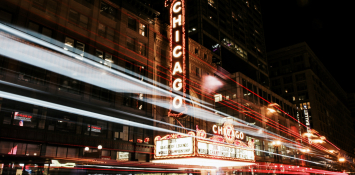 A street at nighttime with a glowing Chicago sign