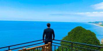 A man stands at an ocean overlook