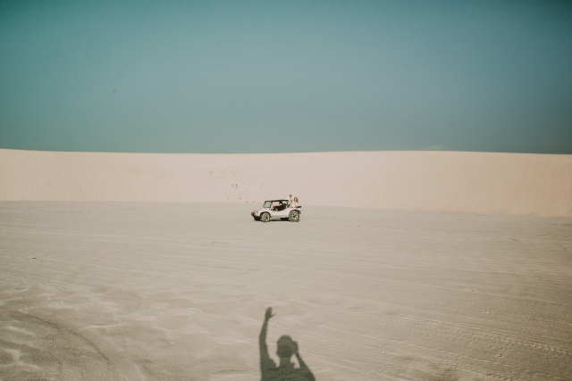A person takes a photo of a jeep in sand dunes