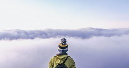 a person with a backpack looks out at clouds.