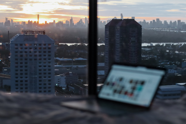 A laptop sits on a table near a window with a city view