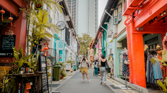 A woman takes a photo in a colorful Singapore street